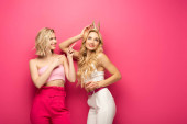 Fotografie Smiling girl pointing with fingers at attractive blonde friend in crown on pink background