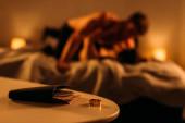 Szelektív összpontosítás pénztárca közelében jegygyűrű és sziluettek férfi prostituált a hálószobában