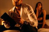 Selektiver Fokus des Geschäftsmannes mit Geldbörse und Geld in der Nähe von Prostituierten auf Bett im Schlafzimmer