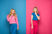 Photo Attractive blonde sisters with fingers near mouths looking away on pink and blue background