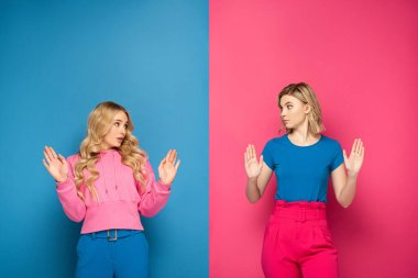 Confused blonde girls showing stop gesture on pink and blue background stock vector