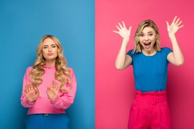 Blonde woman showing stop sign near excited sister on pink and blue background
