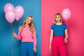 Mosolygó és szomorú szőke lányok kezében lufik kék és rózsaszín háttér