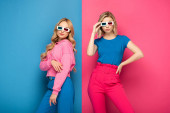 Beautiful blonde girls in 3d glasses on blue and pink background