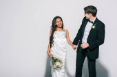 eleganter Bräutigam hält Hand einer glücklichen afrikanisch-amerikanischen Braut mit Brautstrauß auf weißem Hintergrund