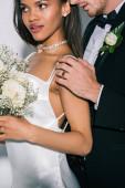 Fotografie oříznutý pohled na ženicha dotýkat rameno krásné africké americké nevěsty drží svatební kytice na bílém pozadí