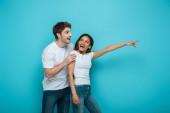 meglepett férfi megható váll mosolygós afro-amerikai lány ujjal mutogató kék háttér