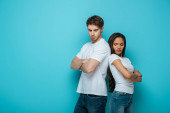 offended interracial couple standing back to back with crossed arms on blue background