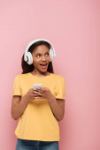 cheerful african american girl in wireless headphones using smartphone while looking away on pink background