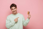 smiling young man pointing with finger at credit card while looking at camera on pink background