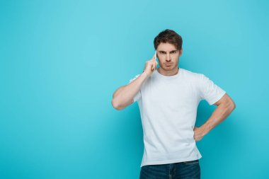 displeased man holding had on hip while talking on smartphone on blue background