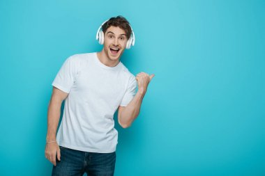 Excited young man in wireless heaphones pointing with thumb while looking at camera on blue background stock vector