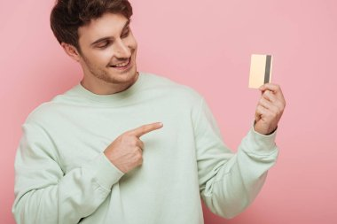 Smiling young man pointing with finger at credit card on pink background stock vector