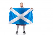 Scottish redhead man in red kilt with flag of Scotland on white background