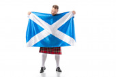 Photo Scottish redhead man in red kilt looking at flag of Scotland on white background
