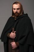 Fotografie ernster mittelalterlicher schottischer Rotschopf im Mantel auf grauem Hintergrund