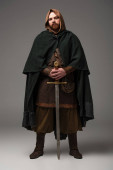 medieval Scottish redhead knight in mantel with sword on grey background
