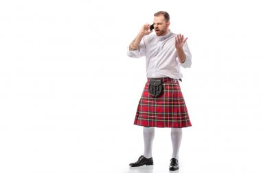 Irritated Scottish redhead man in red kilt talking on smartphone on white background stock vector