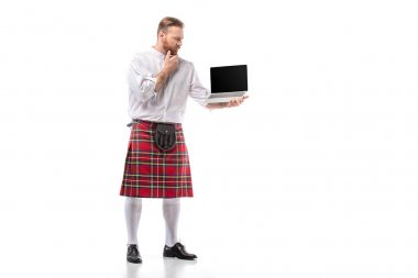 Pensive Scottish redhead man in red kilt holding laptop with blank screen on white background stock vector
