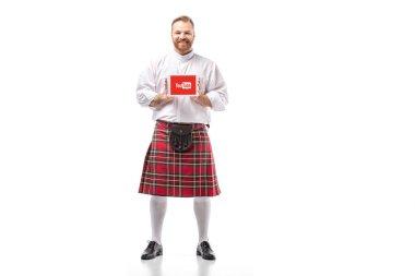 KYIV, UKRAINE - NOVEMBER 29, 2019: smiling Scottish redhead man in red kilt presenting digital tablet with youtube app on white background stock vector