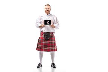KYIV, UKRAINE - NOVEMBER 29, 2019: smiling Scottish redhead man in red kilt presenting digital tablet with tiktok app on white background stock vector