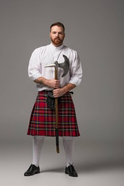 Scottish redhead man in red kilt with battle axe on grey background stock vector