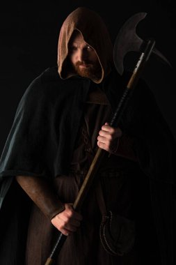 frowning medieval Scottish warrior with battle axe in mantel isolated on black