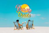 Fotografie zadní pohled na mladý pár sedící v lehátkách s kokosovými nápoji na písečné pláži, sny se vyplní ilustrace
