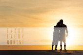 Photo silhouettes of man and woman hugging on beach against sun during sunset, enjoy every moment illustration