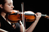 attractive female musician playing symphony on violin isolated on black