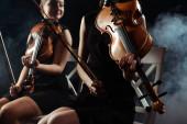 Ausgeschnittene Ansicht attraktiver Musiker, die auf Geigen auf dunkler Bühne mit Rauch spielen