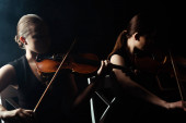 dva hudebníci hrající klasickou hudbu na housle na temném pódiu