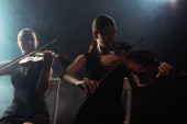 female musicians playing classical music on violins on dark stage with smoke
