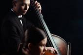 professzionális zenészek hegedűn játszanak és csempésznek a sötét színpadon