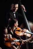 Fotografie trio of smiling musicians playing on double bass and violins isolated on black