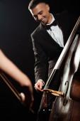Fotografie Lächelnde Profimusiker auf Geige und Kontrabass auf dunkler Bühne