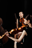 Photo professional positive musicians playing classical music on violins on dark stage