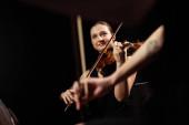 Lächelnde Profimusiker spielen klassische Musik auf Geigen auf dunkler Bühne