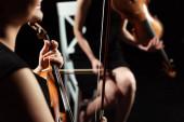 Teilansicht professioneller Musikerinnen auf Geigen auf dunkler Bühne, selektiver Fokus