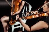 vágott kilátás zenészek játszanak hegedűn a sötét színpadon
