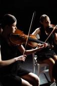 Fotografie attraktive professionelle Musikerinnen, die klassische Musik auf Geigen auf dunkler Bühne spielen