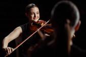 glückliche Profimusiker, die klassische Musik auf Geigen auf dunkler Bühne spielen