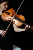 attraktive Musikerin spielt Geige auf dunkler Bühne