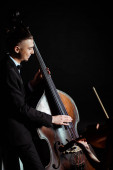 happy professional musicians playing on violin and contrabass on dark stage