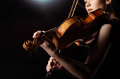 attractive female musician playing on violin on dark stage