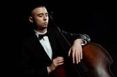 junger Musiker spielt auf Kontrabass isoliert auf schwarz