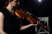 gyönyörű női zenész játszik hegedűn fekete háttér fény
