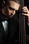 professionelle gut aussehende Musikerin spielt auf Kontrabass isoliert auf schwarz