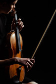 attractive musician playing symphony on violin isolated on black