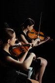 Photo two professional musicians playing classical music on violins on dark stage
